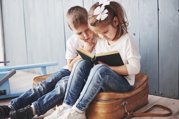 Klaar voor grote reizen. gelukkige meisje en jongen die interessant boek lezen die een grote aktentas dragen. vrijheid en verbeelding concept