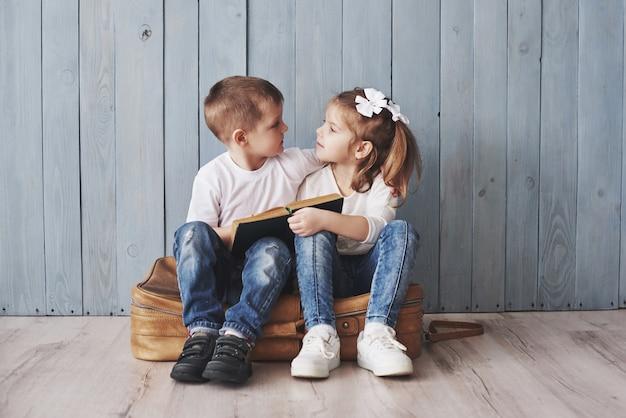 Klaar voor grote reizen. gelukkige meisje en jongen die interessant boek lezen die een grote aktentas en het glimlachen dragen. reizen, vrijheid en verbeelding