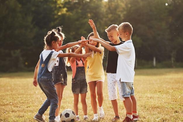 Klaar voor het spel. jonge sportieve kinderen met voetbal staan samen in het veld op een zonnige dag.