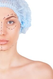 Klaar voor operatie. bijgesneden afbeelding van mooie jonge shirtless vrouw in medische hoofddeksels en schetsen op gezicht camera kijken terwijl geïsoleerd op wit