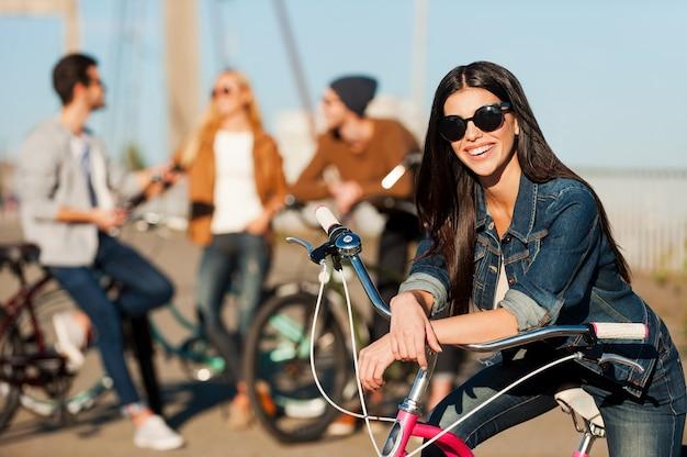Klaar voor plezier en avonturen. mooie jonge glimlachende vrouw die op haar fiets leunt en naar de camera kijkt terwijl haar vrienden op de achtergrond praten