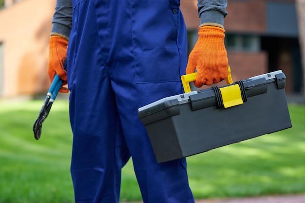Klaar voor renovatiewerkzaamheden. close up van bouwer uitvoering gereedschapskist op bouwplaats