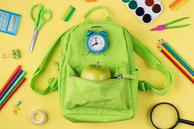 Klaar voor schoolconcept. boven boven bovenaanzicht foto van blauwe wekker appel groene rugzak kleurrijke briefpapier geïsoleerd op gele achtergrond