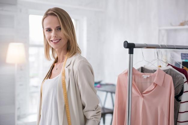 Klaar voor werk. vrolijke vrouwelijke kleermaker poseren in showroom en camera kijken