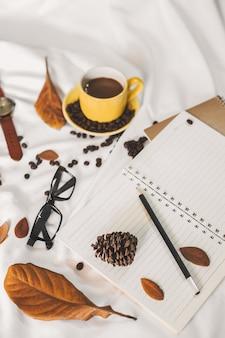 Kladblok brief kopje koffie en een boek met een deken op een witte textiel in bed.