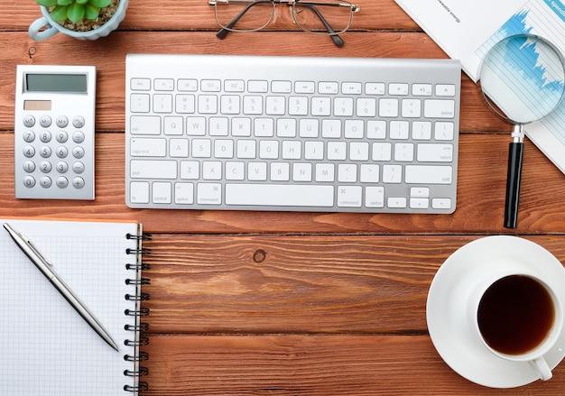 Kladblok, computer en koffie op een houten tafel. zakelijke items achtergrond
