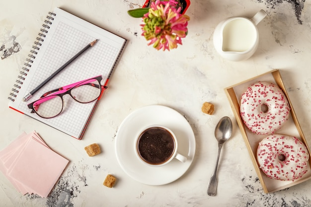 Kladblok, donuts en koffie op witte tafel