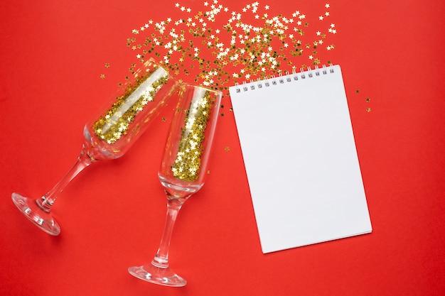 Kladblok en champagneglazen met gouden sterren confetti, kerstmis en nieuwjaar concept