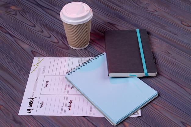 Kladblok en clender op het houten bureau. koffiepauze concept.