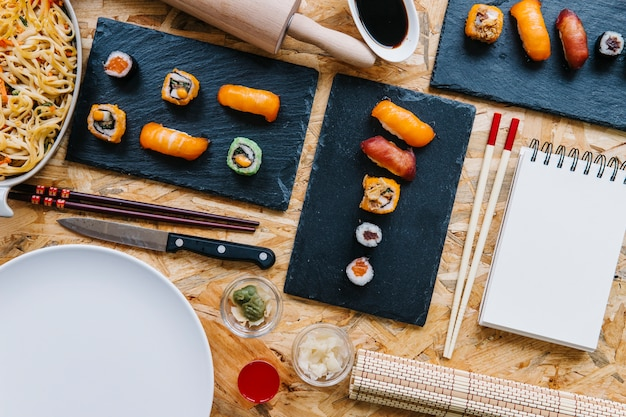 Kladblok en eetstokjes in de buurt van sushi