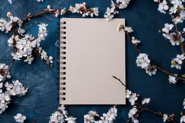 Kladblok en kersen takken met lentebloemen op een donkerblauwe achtergrond
