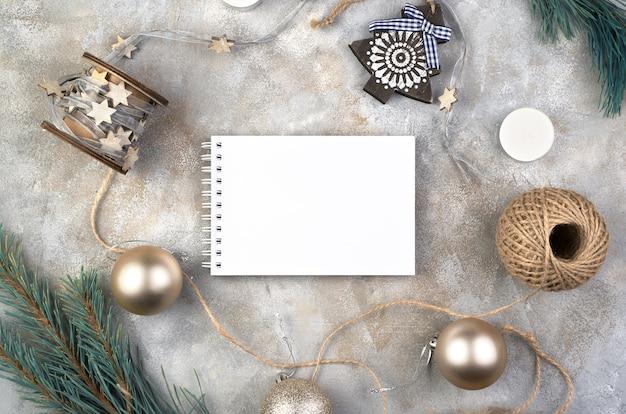 Kladblok en kerstmisspeelgoed, schaatsen, ster en ballen op een grijze ondergrond.