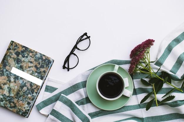 Kladblok en kopje koffie op witte achtergrond.