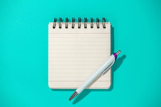 Kladblok en pen op blauwe achtergrond, bovenaanzicht