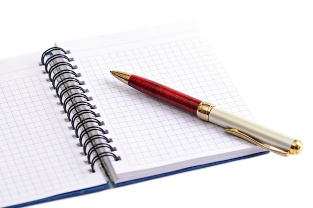 Kladblok en pen op witte achtergrond