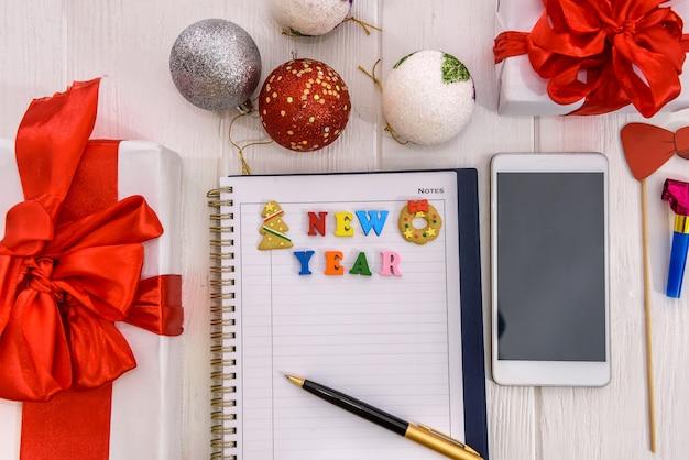 Kladblok en telefoon op tafel met resolutie voor het nieuwe jaar