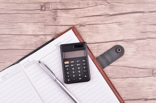 Kladblok geopend met leeg gebied voor tekst of bericht, pen en rekenmachine op houten tafel