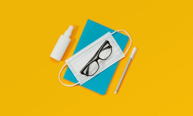 Kladblok glazen pen masker en ontsmettingsmiddel tegen een oranje achtergrond