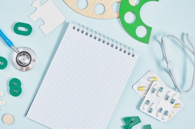 Kladblok, kinderen bril, stethoscoop, pillen en speelgoed op een blauwe achtergrond