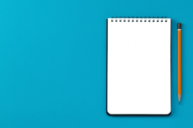 Kladblok kopie ruimte en potlood op een blauwe muur bovenaanzicht.