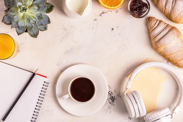 Kladblok, koptelefoon, croissants en koffie op witte tafel.