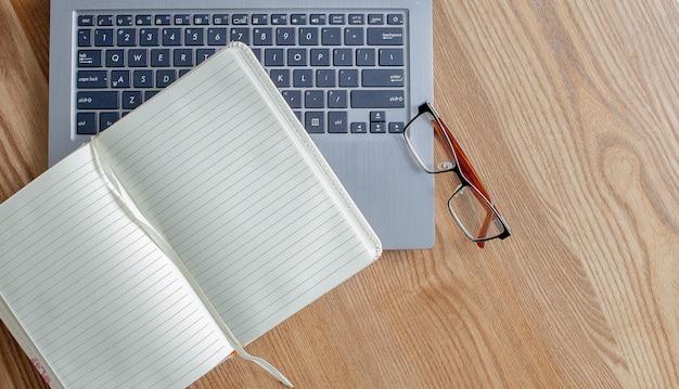 Kladblok, laptop en glazen op oude houten bureau. bekijk van bovenaf met kopie ruimte in vintage toon