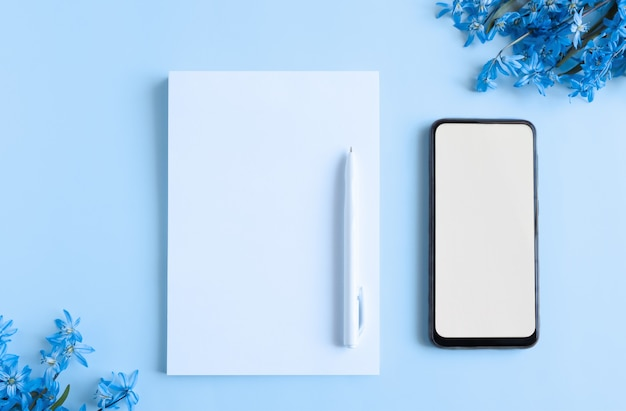 Kladblok met blanco witte vellen op een blauwe achtergrond met bovenaanzicht van plantenelementen