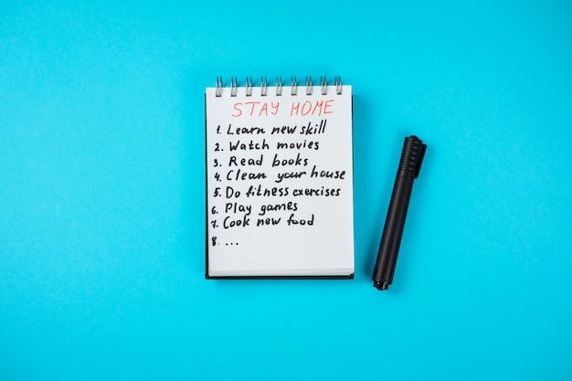 Kladblok met checklist voor thuis blijven op covid 19 quarantaine. blijf thuis, blijf veilig. lees boeken, speel games, kijk films, leer nieuwe vaardigheden, maak je huis schoon, doe aan fitness, kook een nieuwe maaltijd.