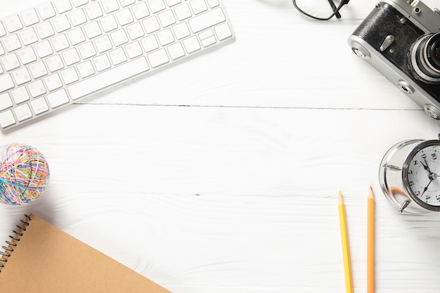 Kladblok met computer en camera op de werktafel