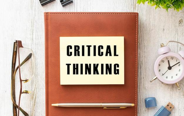 Kladblok met de tekst critical thinking op een houten tafel. bruin dagboek en pen