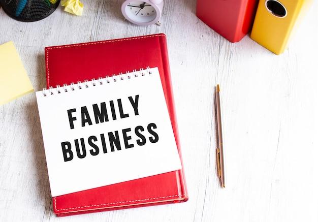 Kladblok met de tekst family business op een houten tafel. rode dagboek en pen.