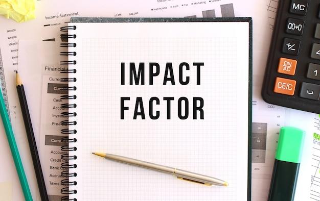 Kladblok met de tekst impact factor op het bureau, in de buurt van kantoorartikelen.