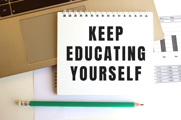 Kladblok met de tekst keep educating yourself staat op het toetsenbord van de laptop. bedrijfsconcept.