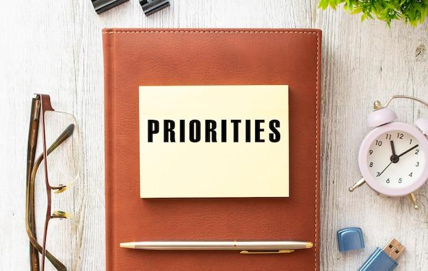 Kladblok met de tekst prioriteiten op een houten tafel. bruin dagboek en pen.