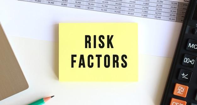 Kladblok met de tekst risicofactoren op het bureaublad
