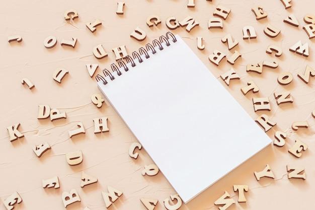 Kladblok met een open blanco pagina en houten letters op een lichte ondergrond. plat leggen
