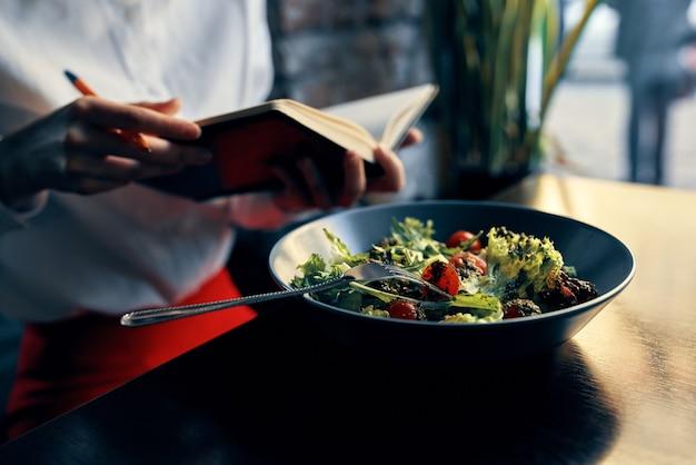 Kladblok met een pen in de hand en salade in de inscriptie van een plaatrestaurant