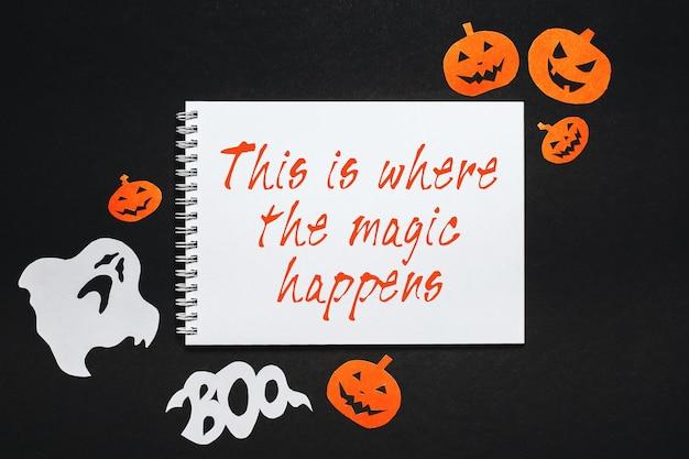 Kladblok met halloween-tekst dit is waar de magie op zwarte achtergrond gebeurt