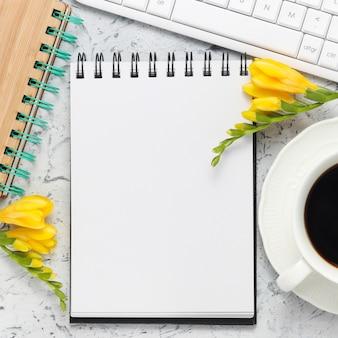 Kladblok met kopie ruimte voor tekst of felicitatie wit toetsenbord kopje koffie werkplek
