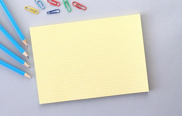 Kladblok met lege ruimte voor tekst op een grijze ondergrond naast potloden en paperclips.