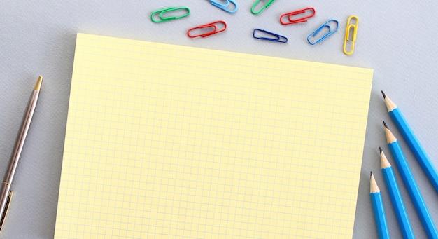 Kladblok met lege ruimte voor tekst op een grijze ondergrond naast potloden, pen en paperclips.