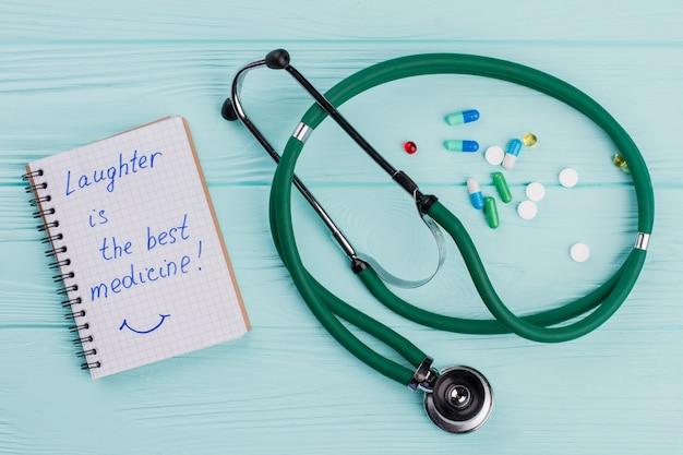 Kladblok met medische stethoscoop en in de buurt van drug pillen liggend op blauwe achtergrond. lachen is het beste medicijn op het notitieblok.