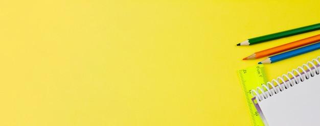 Kladblok met potloden op een gele achtergrond.