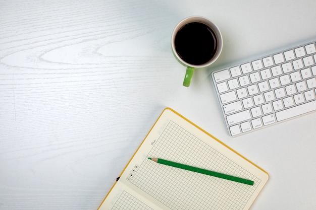 Kladblok met potlood toetsenbord en kopje koffie