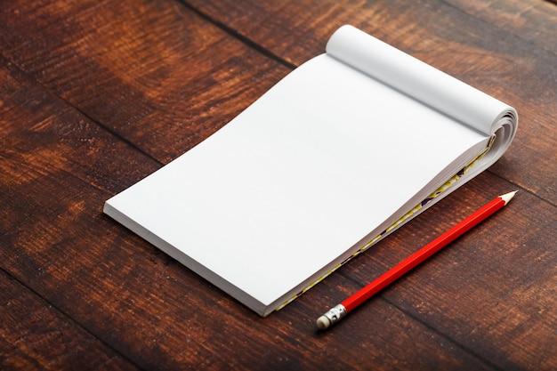 Kladblok met rood potlood op een bruine houten tafel achtergrond, voor onderwijs, schrijf doelen en daden