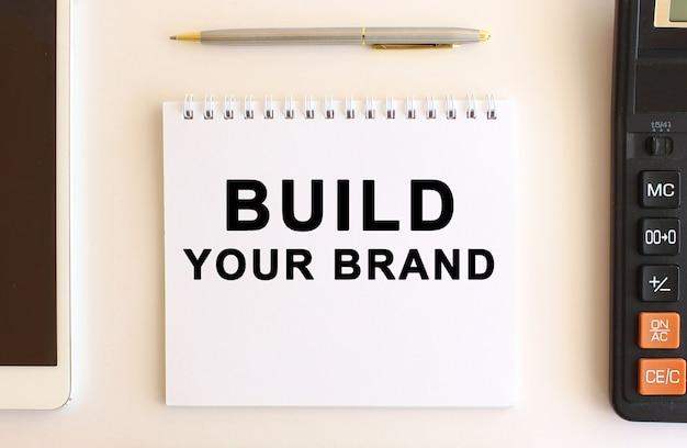 Kladblok met tekst bouw je merk, in de buurt van rekenmachine, tablet en pen. bedrijfsconcept.