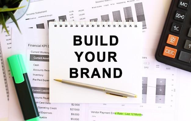 Kladblok met tekst bouw je merk op een witte ondergrond. bedrijfsconcept.