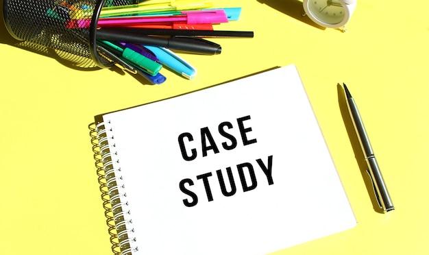 Kladblok met tekst case study met briefpapier. gele achtergrondkleur. bedrijfsconcept.