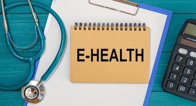 Kladblok met tekst e-health, rekenmachine en stethoscoop