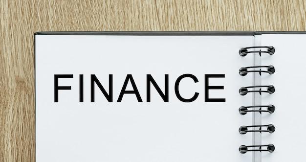 Kladblok met tekst finance op houten bureau. zakelijk en financieel concept